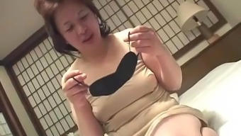 Asian Granny Arch Supports A Replica Toy Gun In Their Pussy